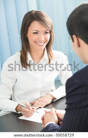 Two businesspeople, or business person and client, with document at office