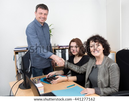 Two Businesspeople shaking hand in front of colleague In Office - stock photo