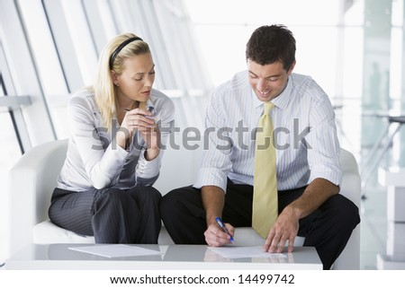 Two businesspeople sitting in office lobby talking and smiling - stock photo