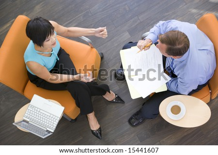 Two businesspeople sitting indoors with coffee laptop and folder - stock photo