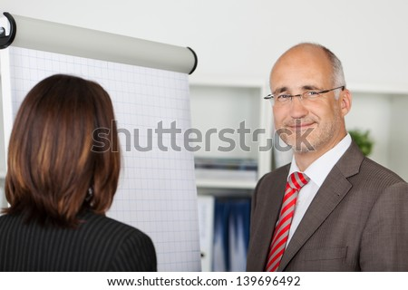 two businesspeople standing by flipchart in office - stock photo