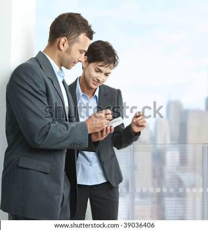 Two businesspeople standing on balcony of downtown office building, using smart mobile phone, smiling. - stock photo