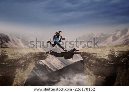 Two businesspeople through the gap as the business obstacle by work together - stock photo