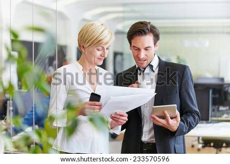 Two Businesspeople with files making decisions in office - stock photo