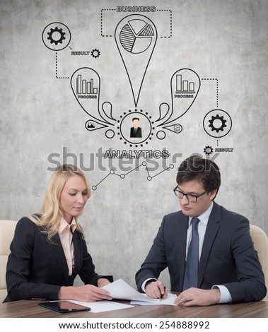 two businesspeople working in office and drawing analytics scheme on wall - stock photo