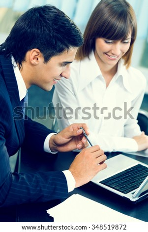 Two businesspeople working together at office. Focus on man
