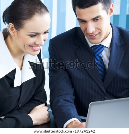 Two businesspeople working with laptop at office - stock photo