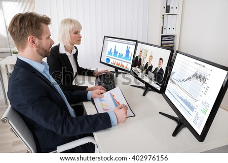 Two Businesspeople Working With Multiple Computer At Office