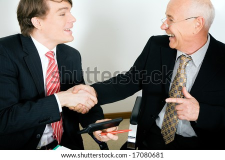 Two Businesspeople (younger and a senior figure) shaking hands agreeing on a deal - stock photo