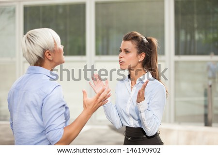 two businesswoman are arguing on the street - stock photo