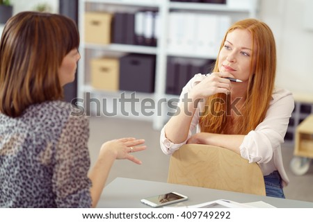 Two businesswoman having an informal meeting with one sitting relaxing on a reversed chair listening to her colleague with a pensive expression