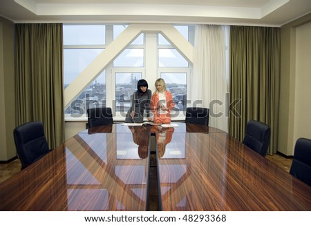 Two businesswoman working in a boardroom