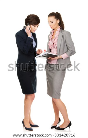 Two businesswomans discussing about their plans. - stock photo
