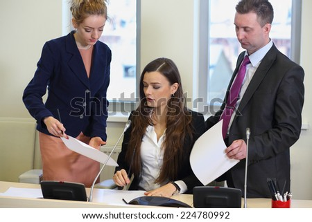 Two businesswomen and man corrected papers in the conference hall - stock photo
