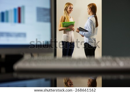 Two businesswomen are discussing in the office corridor - stock photo