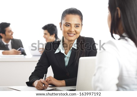 Two businesswomen discussing in an office with their colleagues in the background - stock photo
