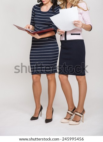 Two businesswomen discussing something and holding documents, white background - stock photo