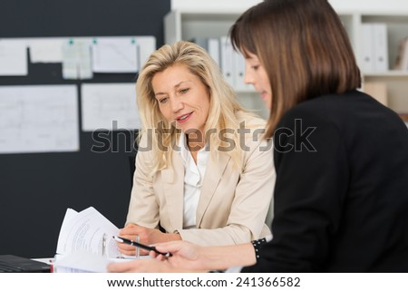 Two businesswomen having a discussion in the office as they examine a paper document making notes on the report - stock photo