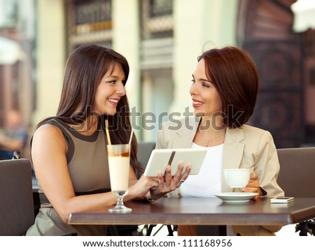 Two businesswomen in a cafe using a digital tablet