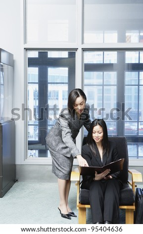 Two businesswomen looking at document