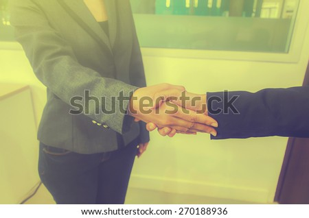 Two Businesswomen Shaking Hands In Office, vintage tone - stock photo