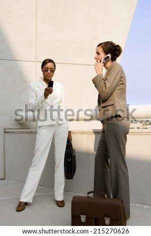 Two businesswomen standing on balcony, using mobile phones