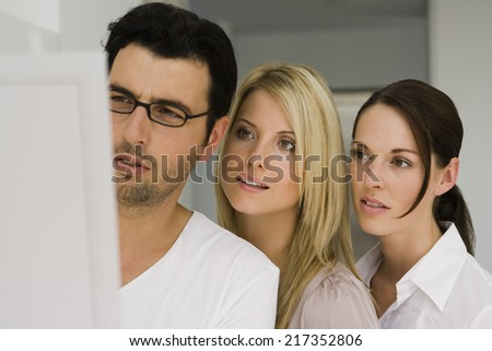 Two businesswomen with a businessman looking at a blueprint