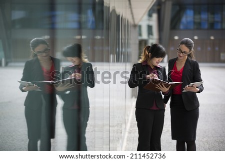 Two businesswomen with digital tablet in a modern urban setting. Caucasian and Asian business women with reflection in glass window. - stock photo
