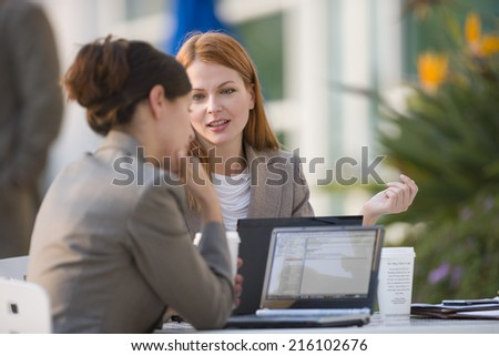 Two businesswomen with laptops working in cafe - stock photo