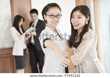 Two businesswomen with their thumbs up in the office - stock photo