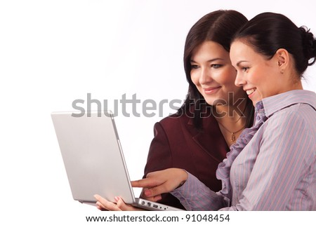 Two businesswomen working together on laptop on white background - stock photo