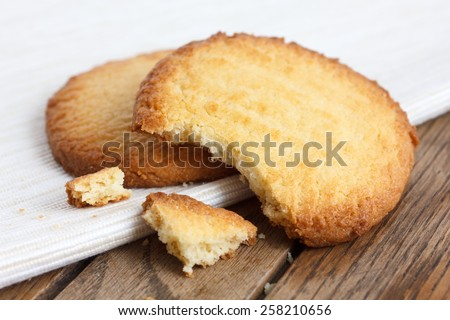 Two butter biscuits on napkin and wood. Broken. - stock photo