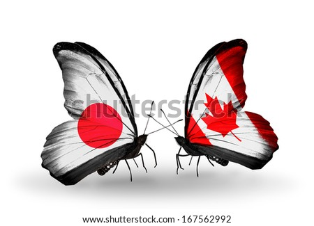 Two butterflies with flags on wings as symbol of relations Japan and Canada - stock photo
