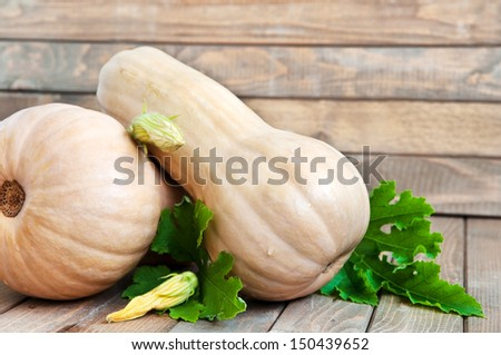 Two butternuts with leaves on wooden table, horizontal