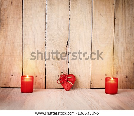 two candles and a wrapped heart shaped gift on wooden background - stock photo