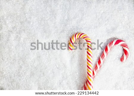 Two Candy Canes On Snowy Background. Copy Space - stock photo