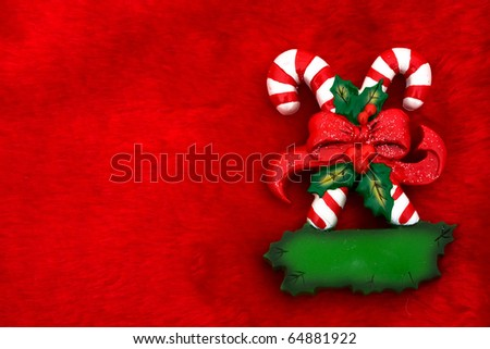 Two candy canes with a bow  on a red textured background, Candy cane - stock photo