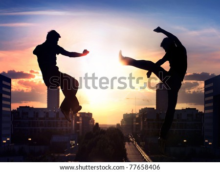 Two capoeira fighters over night city background - stock photo