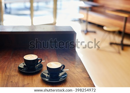 Two cappucinos sitting on a wooden counter in coffee shop - stock photo