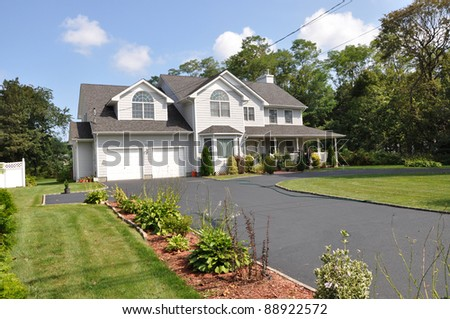Two Car Garage Suburban Home with Long Blacktop Driveway Plants Flower Bed Front Yard Lawn Sunny Blue Sky Clouds Daytime - stock photo
