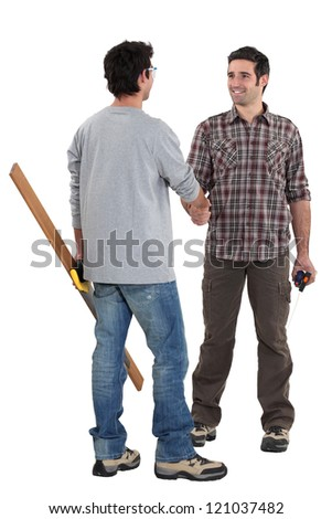 Two carpenters shaking hands - stock photo