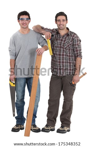 Two carpenters stood with plank of wood - stock photo