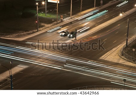 Two cars at a crossroads wait at night a green signal of a traffic light. Night shooting. Bright traces of headlights of cars - stock photo
