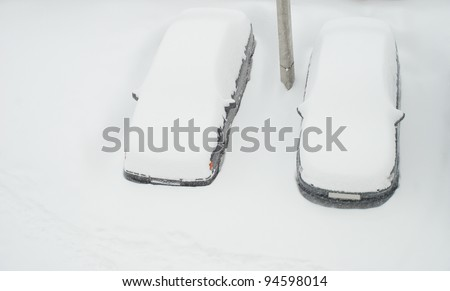 Two cars covered with snow in the winter blizzard