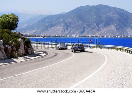 two cars on a sunny coastline road - stock photo