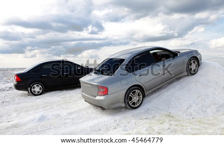 Two cars on snow - stock photo
