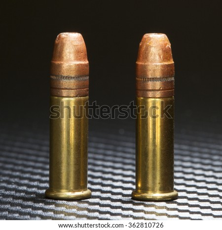 Two cartridges designed for rimfire guns that have copper plated bullets - stock photo