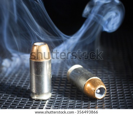Two cartridges for a handgun with lots of smoke around - stock photo