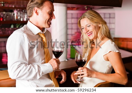 Two (casual) business people in a hotel bar in the evening having glasses of red wine and a little flirt - stock photo
