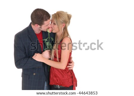 Two casual dressed young adults, teenage man and woman in love, embracing each other. studio shot, reflective surface - stock photo